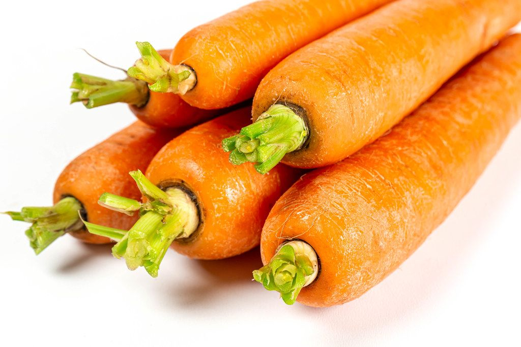 Ripe orange carrots on white, close-up