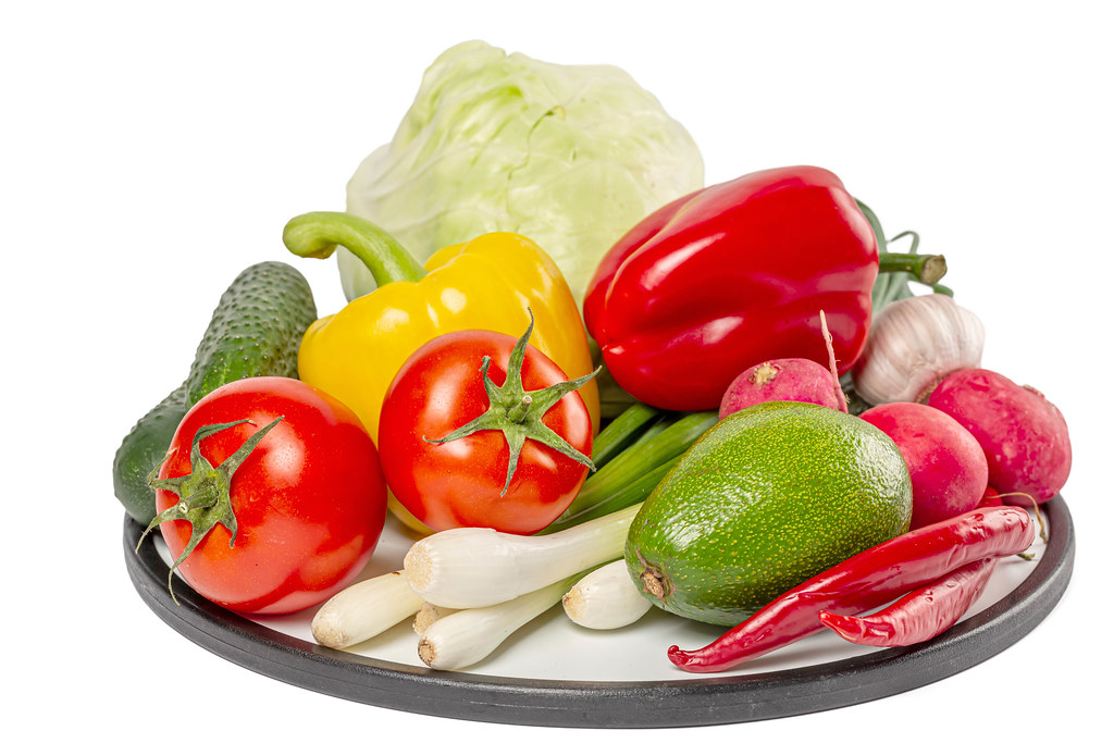 Ripe vegetables on a round kitchen board