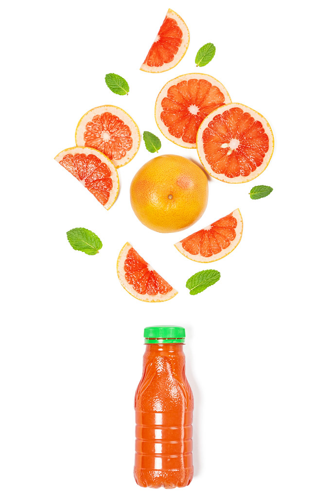 Ripe whole grapefruit and slices with mint leaves on white with a bottle of juice, top view