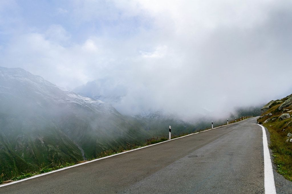 Road high in the Swiss Alps disappearing into the clouds