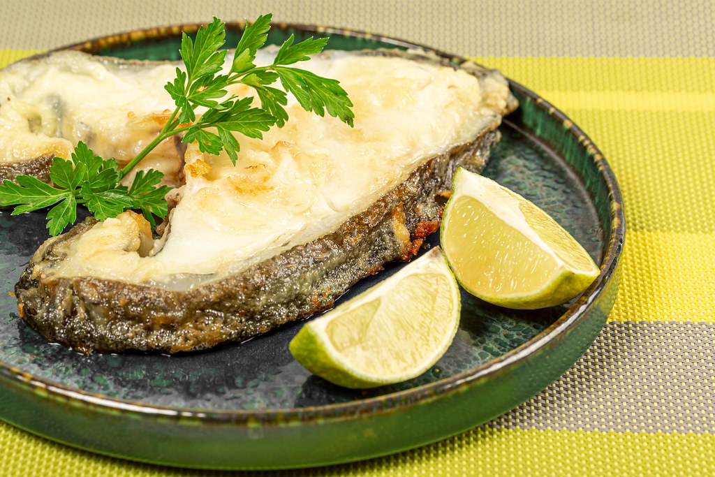 Roasted catfish steak with parsley and lime slices, close up