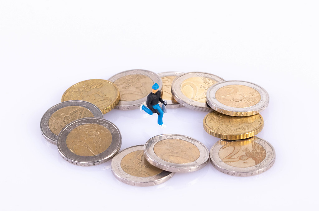 Robber with coins on white background