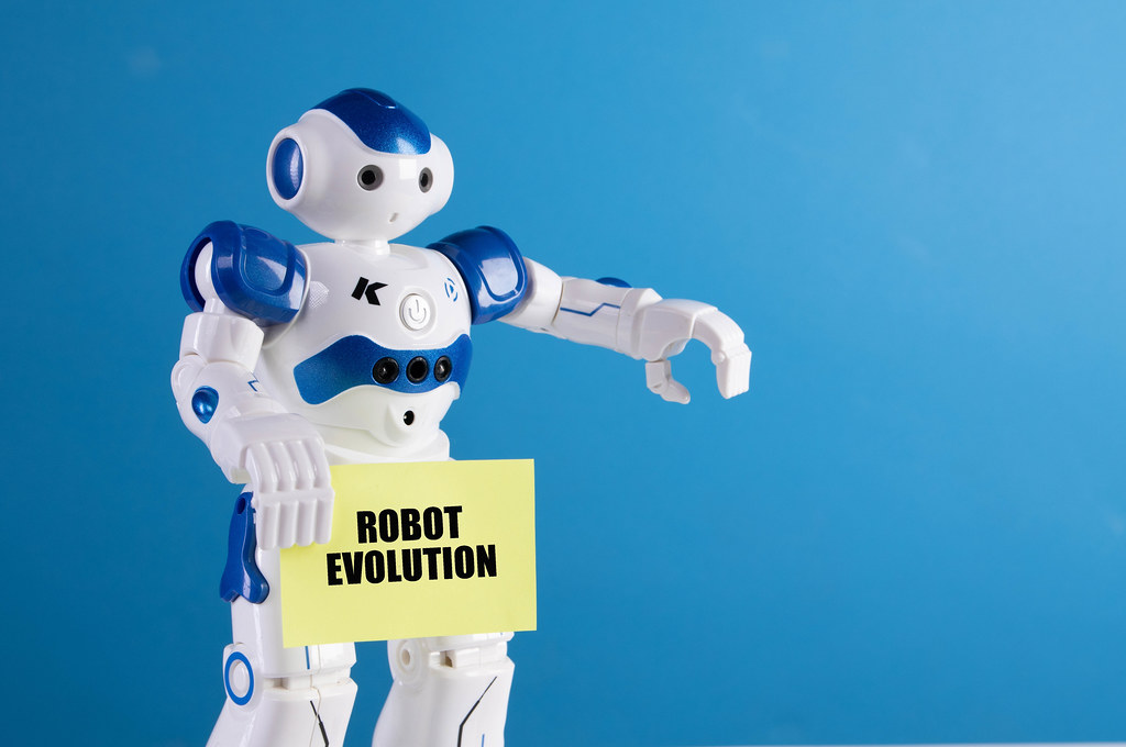 Robot holding a sing with Robot Evolution text
