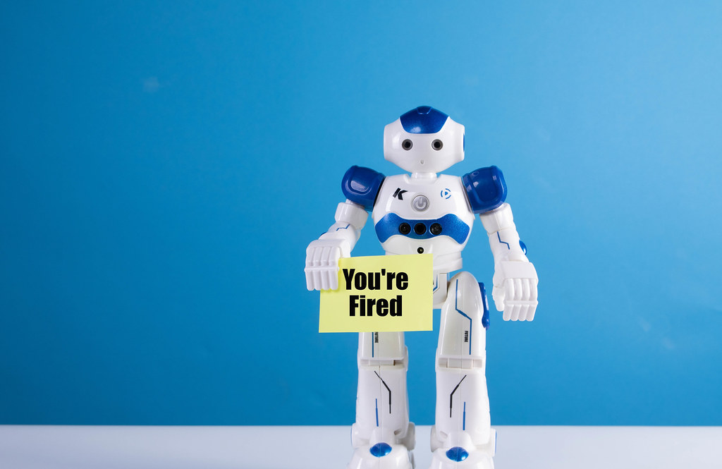 Robot holding a sing with You're fired text