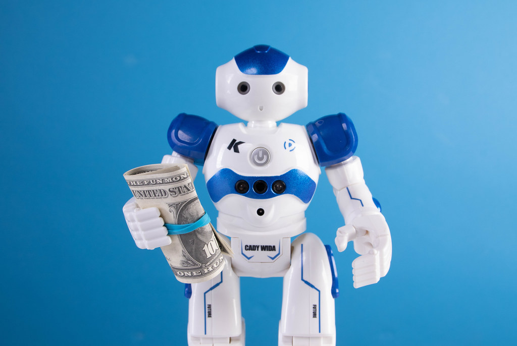 Robot holding dollar banknotes on blue background