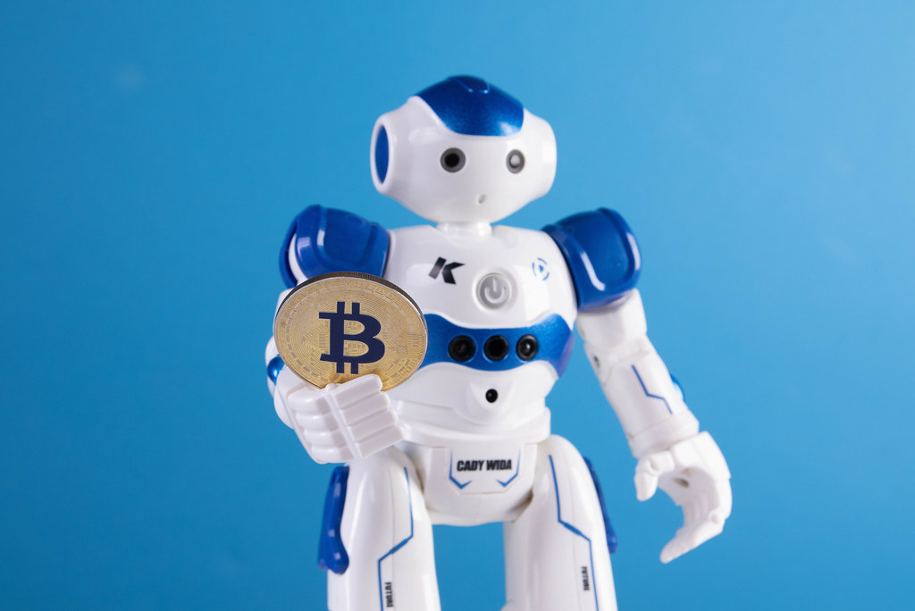 Robot holding golden Bitcoin coin on blue backgorund