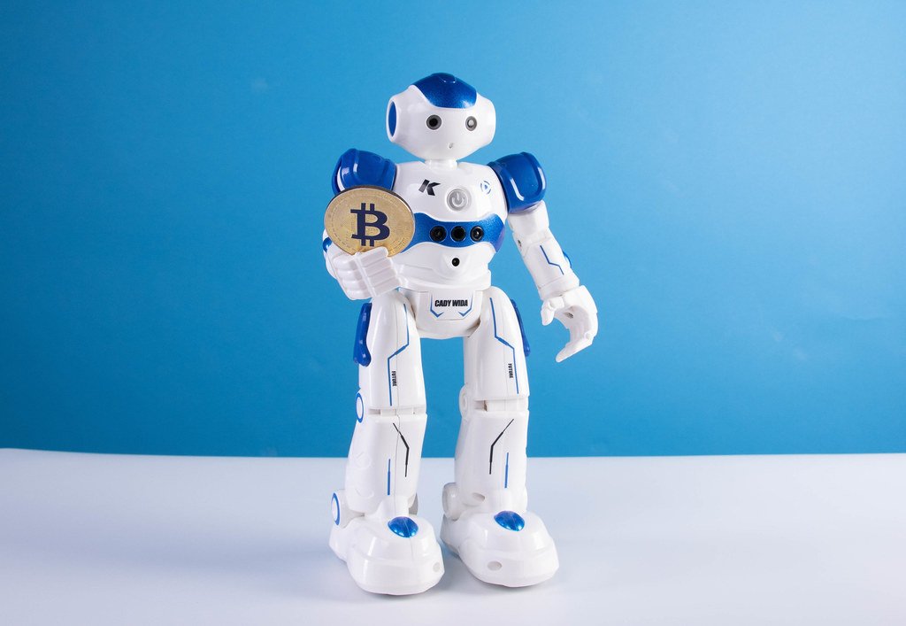 Robot holding golden Bitcoin coin