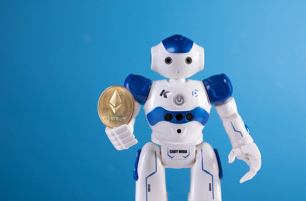 Robot holding golden Ethereum coin