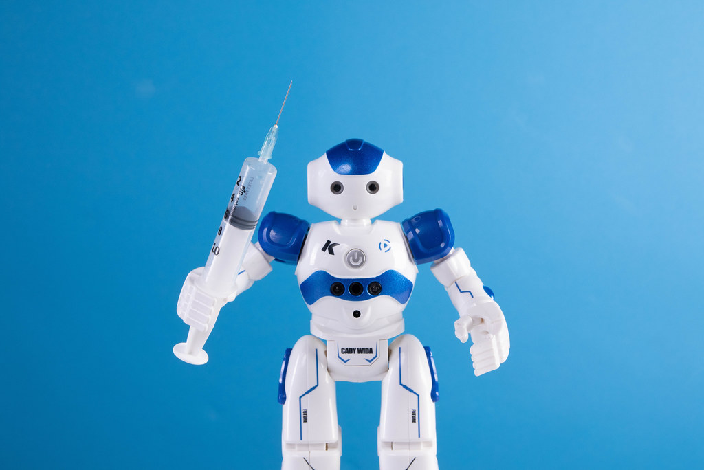 Robot holding syringe on blue background