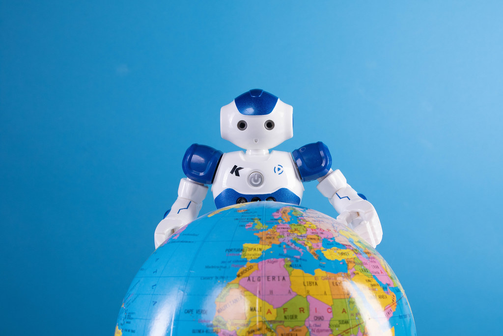 Robot with globe on blue background