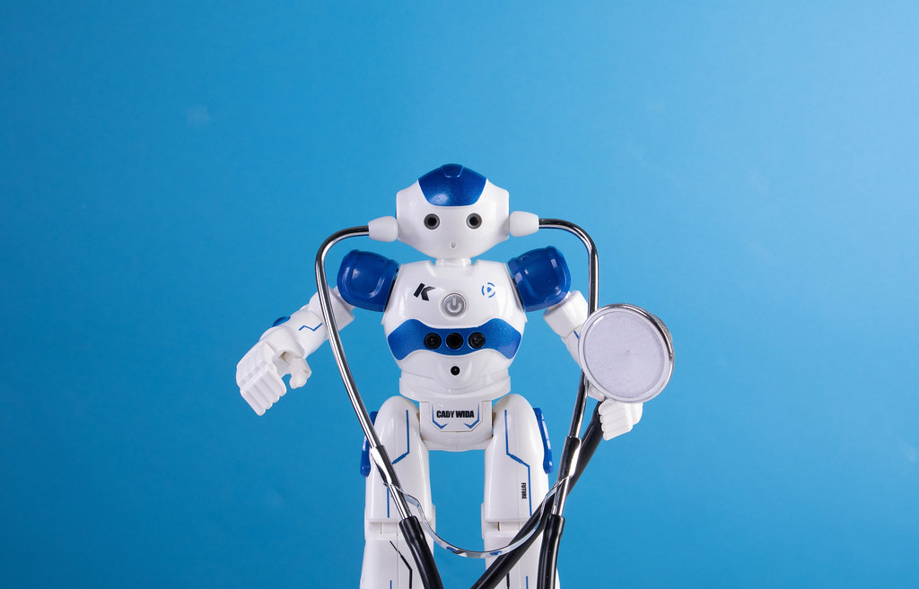 Robot with stethoscope on blue background