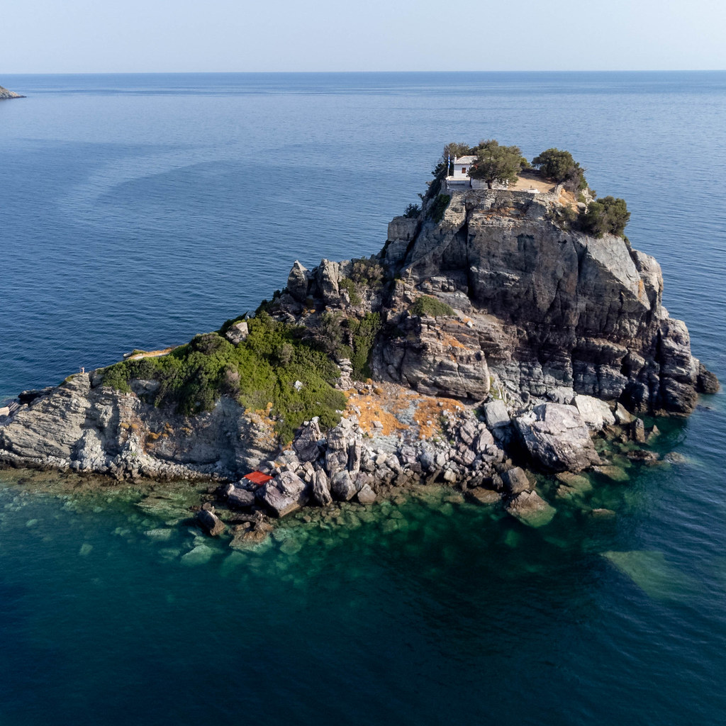 Rock formation surrounded by turquoise waters with chapel and monastery on top: Agios Ioannis, Skopelos