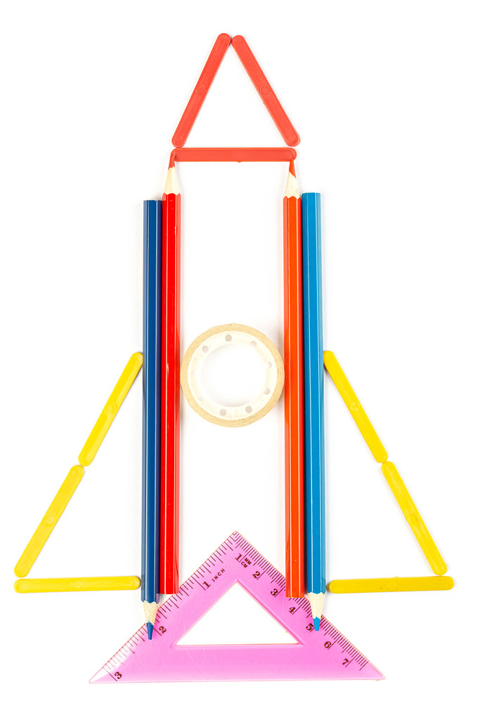 Rocket made from school supplies on white background, top view