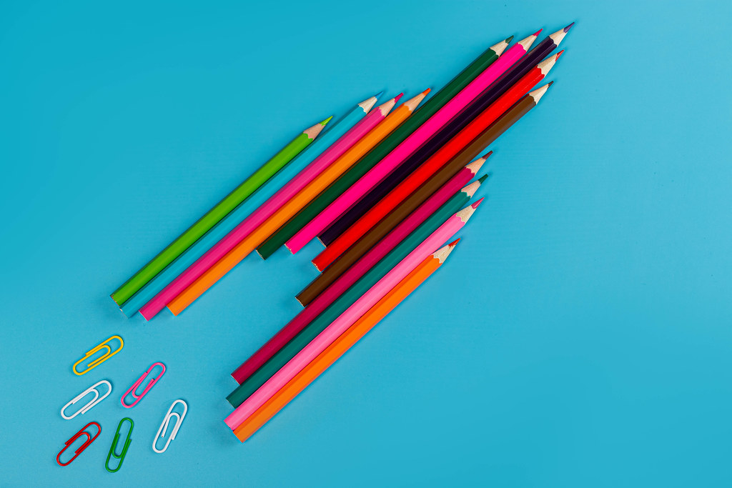 Rocket made of colored pencils and paper clips on blue background
