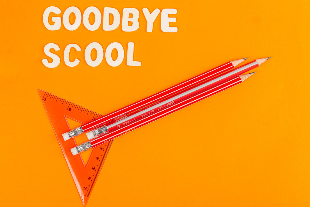 Rocket with pencils and ruler on orange background, goodbye school concept
