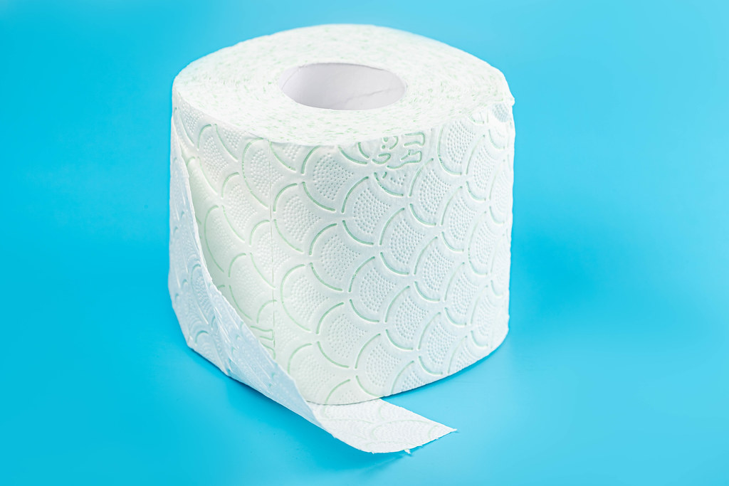 Roll of white toilet paper on blue background