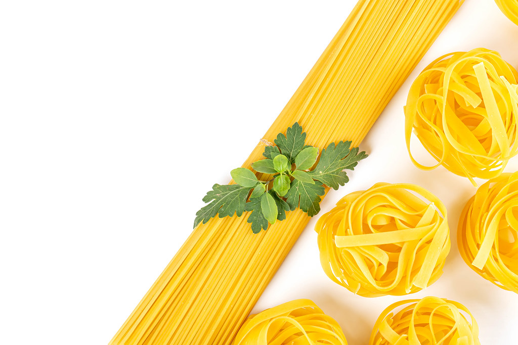 Rolled raw tagliatelle and spaghetti, italian pasta on white background