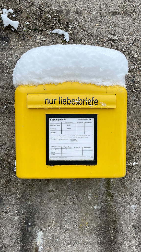 Romanticism: yellow letterbox of Deutsche Post with a sticker