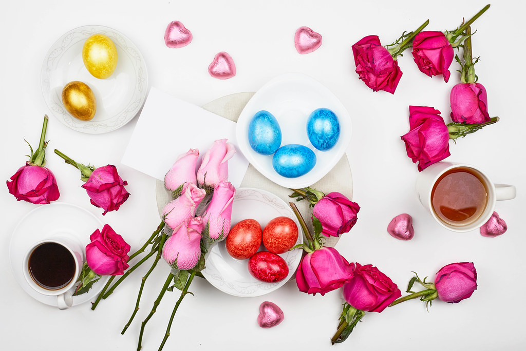 Romantischer Hintergrund zu Ostern mit bunten Eiern, Rosen, Kaffee und Schokoherzen