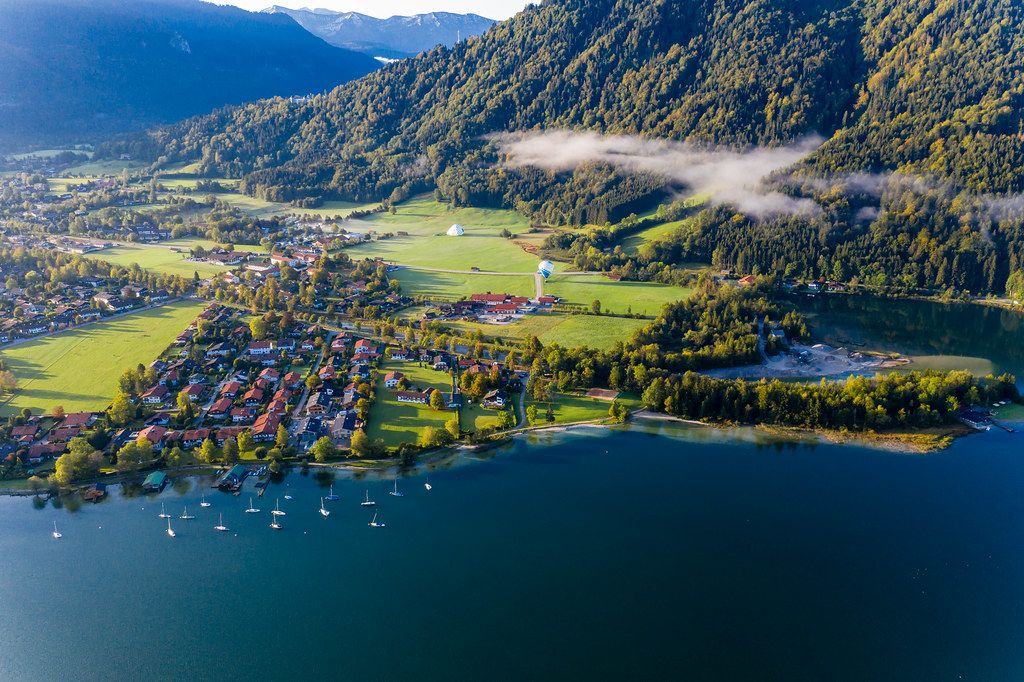 Rottach-Egern (Tegernsee) in autumn light with two hot air balloons at the foot of the Wallberg. Drone pic