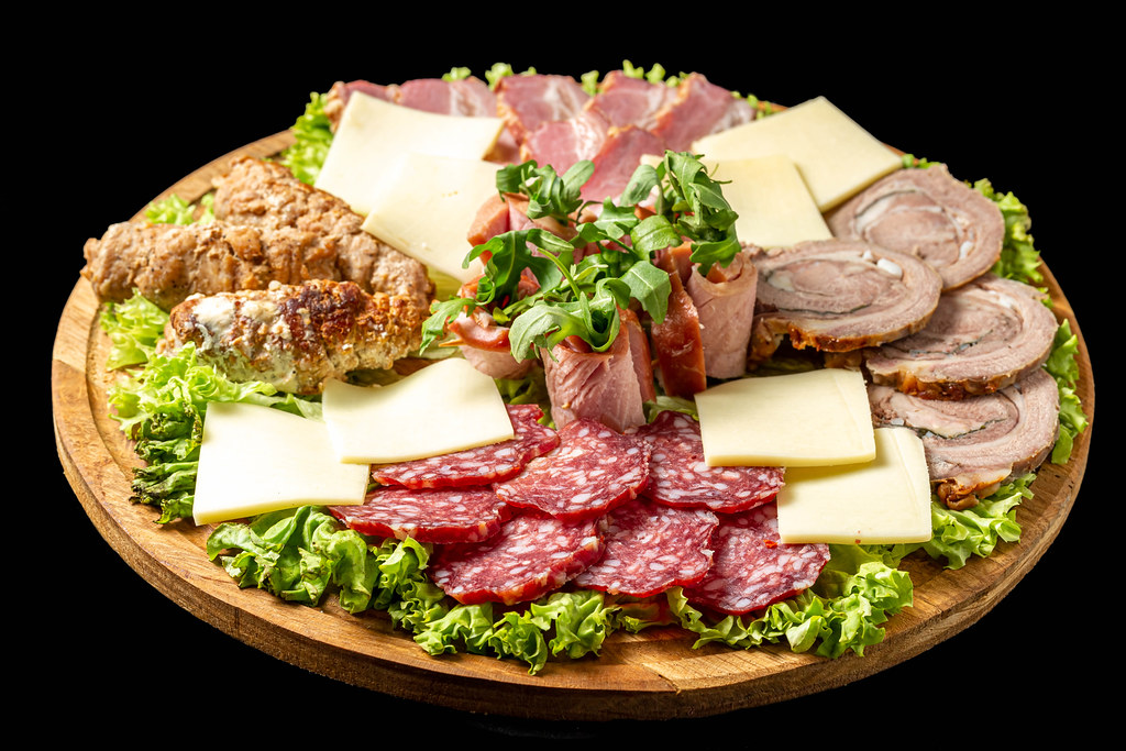 Round board with meat and cheese slices, arugula and lettuce on a black background