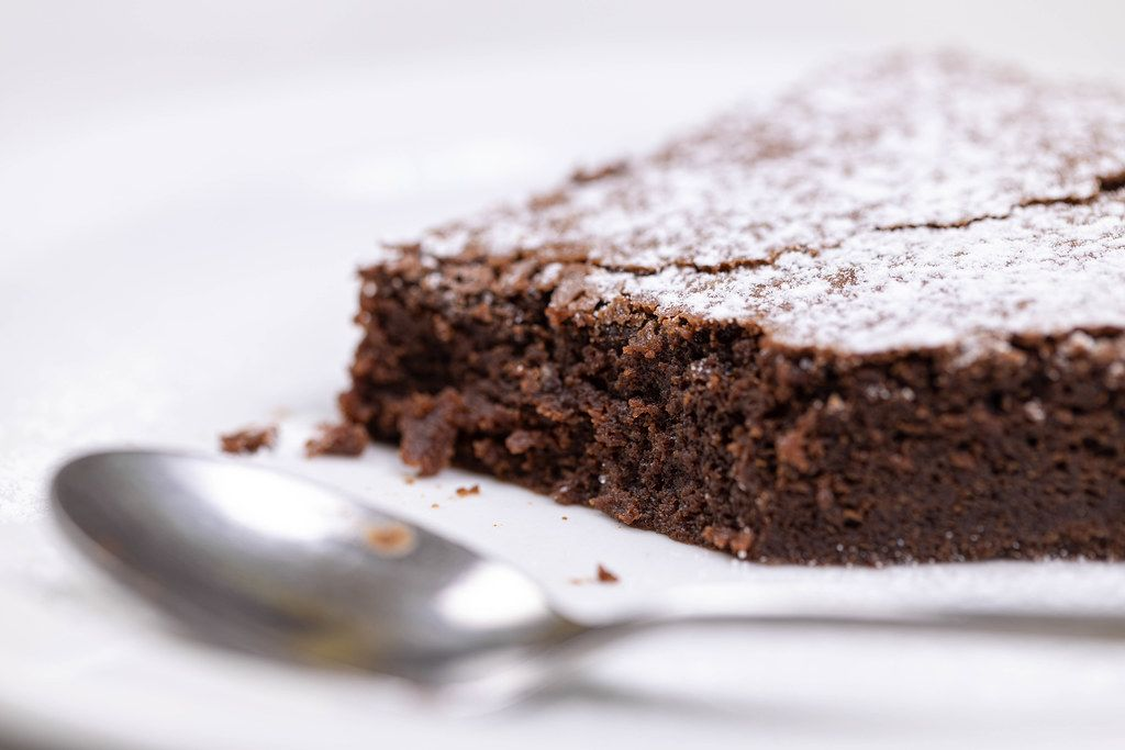 Round Chocolate cake slice with powdered sugar on the plate