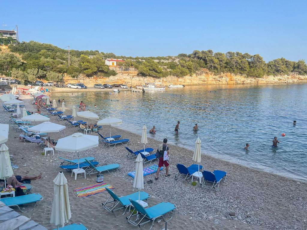Rousoum Gialos beach in Patitiri on Greek island Alonnisos. Pebble beach with white parasols