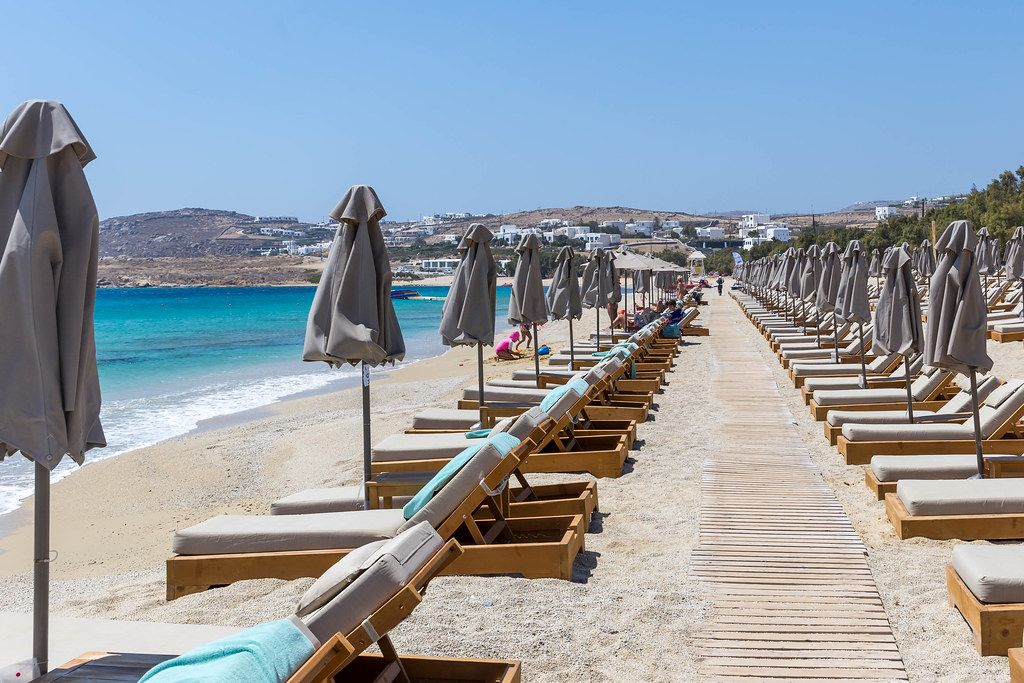 Rows of parasols, emtpy sun beds and a wooden path on the popular Kalafati beach, Mykonos, Greece