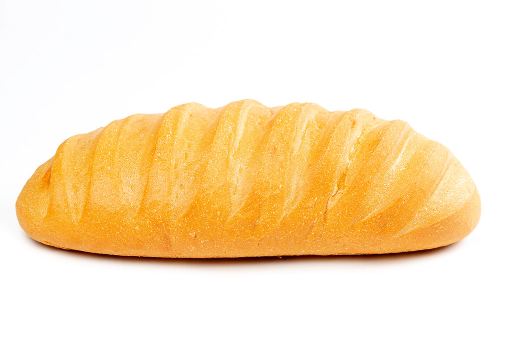 Ruddy long loaf of bread on white background