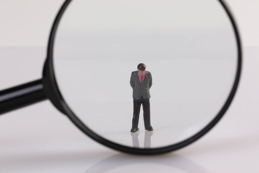 Sad businessman under magnifying glass