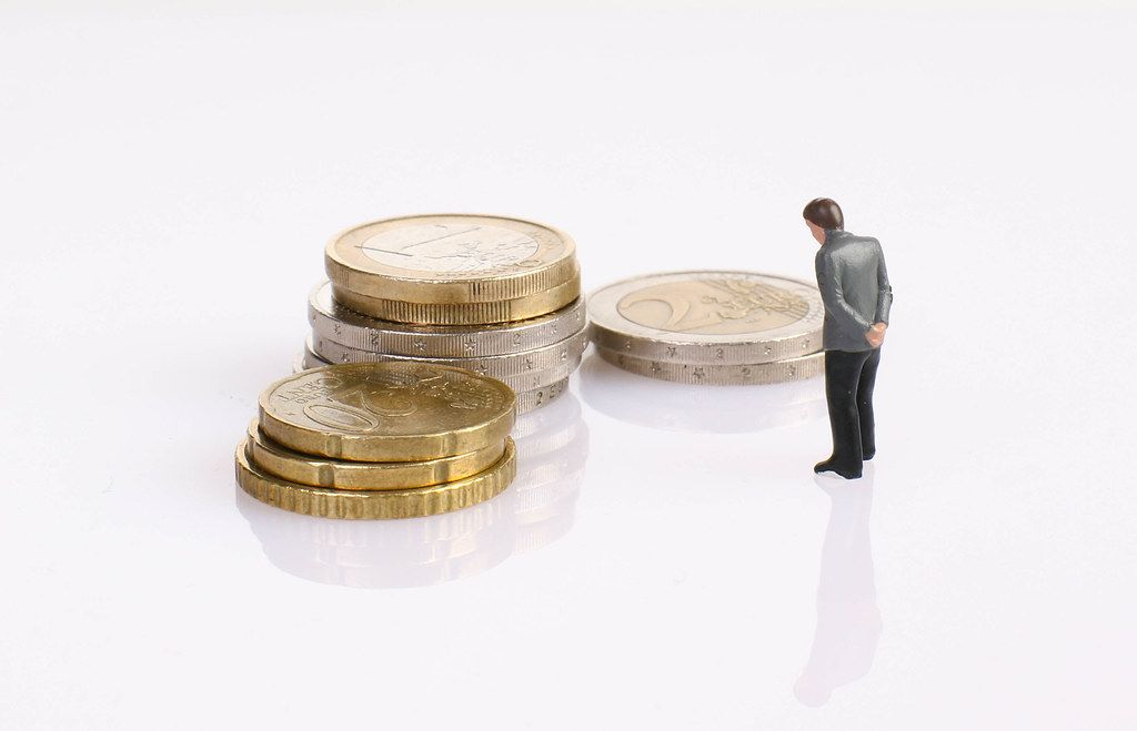 Sad businessman with coin stack on white background