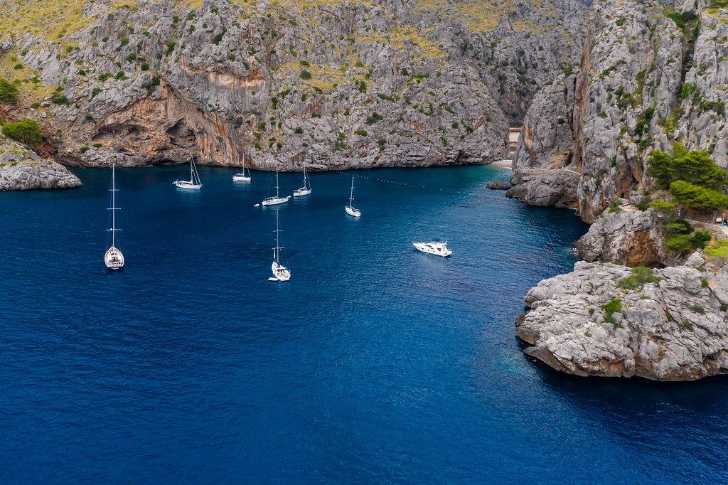 Sailboats and motor boats in front of the steep cliffs of Sa Calobra, northwest coast of Majorca, drone pic