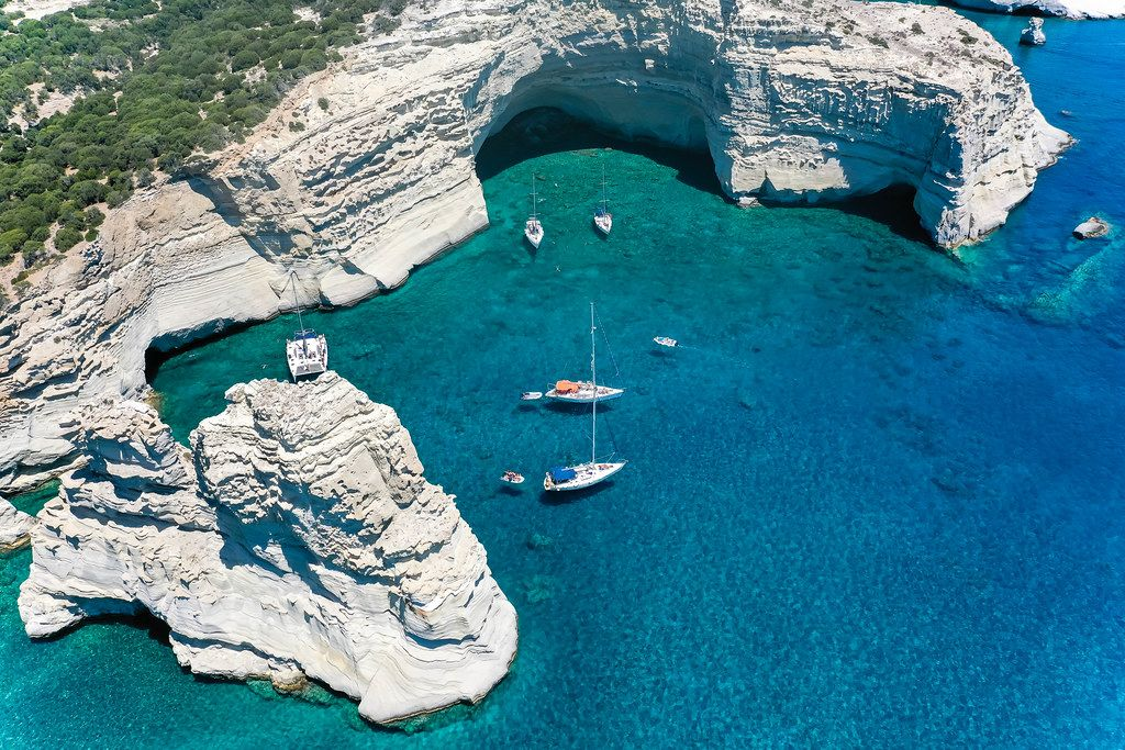 Sailboats and stunning landscape, dream destination in Greece: Kleftiko bay on the island Milos. Drone pic