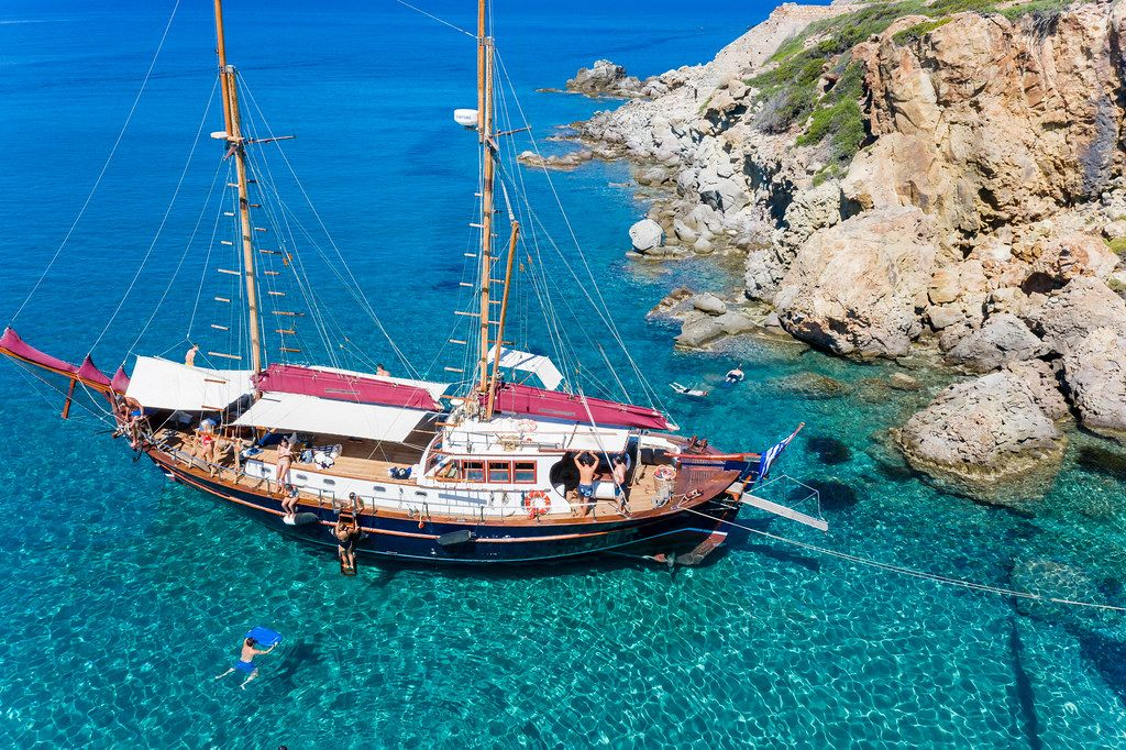 Sailing boat by the coast of Milos in spectacularly clear waters. Tourists swimming and snorkeling