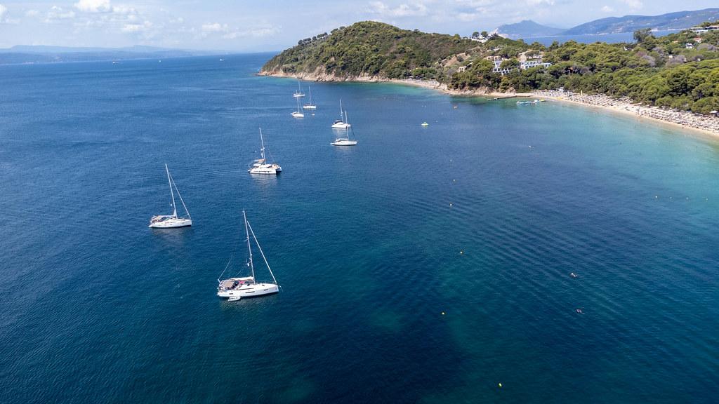 Sailing boats off the coast of Koukounaries, wooded paeninsula and beach on Skiathos