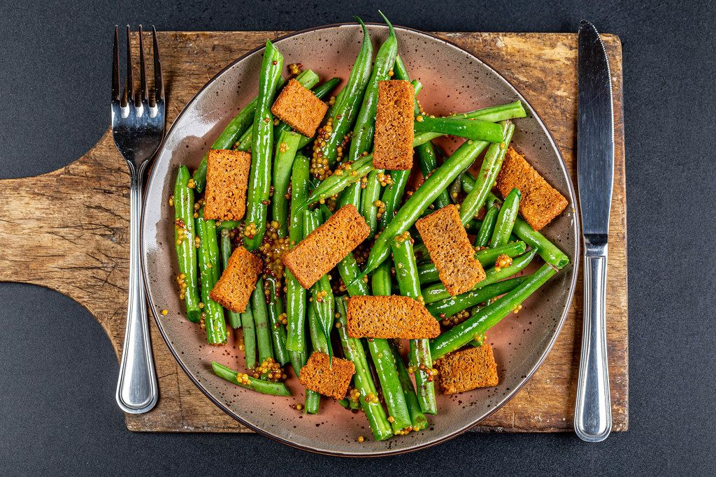 Salad with asparagus and rye rusks with mustard sauce on dark background