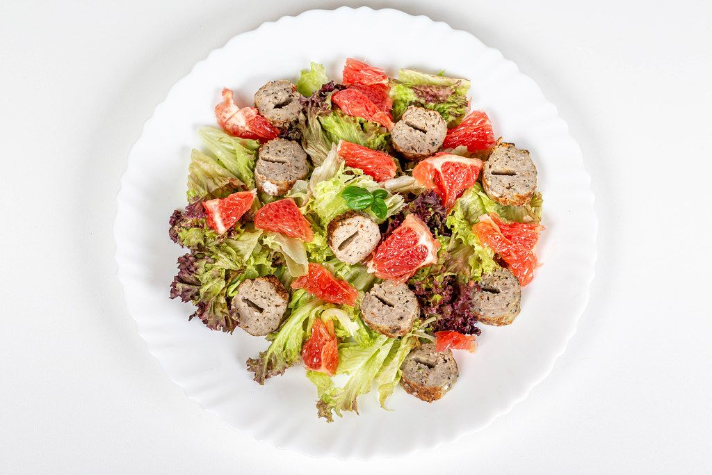 Salad with lettuce, grapefruit and grilled sausage, top view