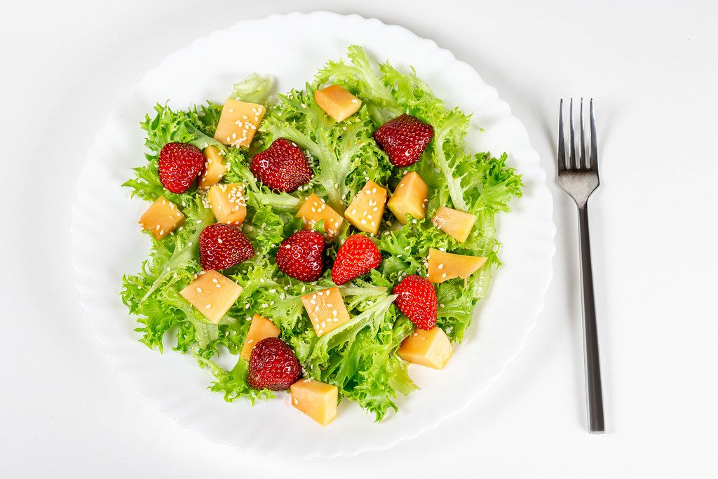 Salad with strawberries, mango, lettuce and sesame seeds. Top view