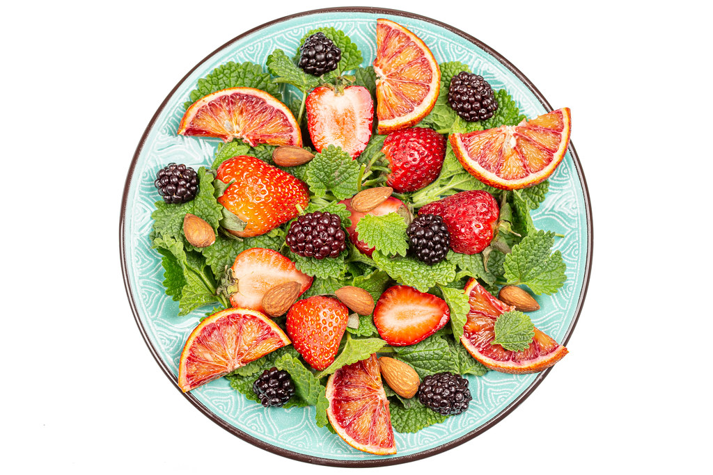 Salad with strawberries, sicilian orange and blackberries, top view