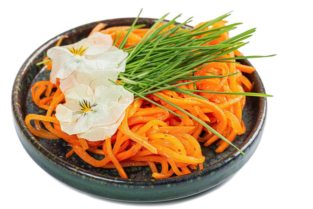 Salad with wheat sprouts, grated carrots and white edible flowers