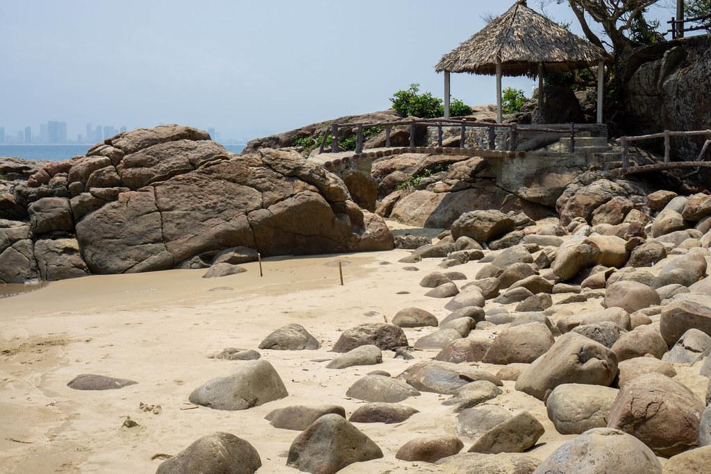 Sandstrand mit großen Steinen, Holzbrücke und kleiner Hütte mit Strohdach auf der Son Tra Halbinsel mit Blick auf die Skyline von Da Nang in Vietnam