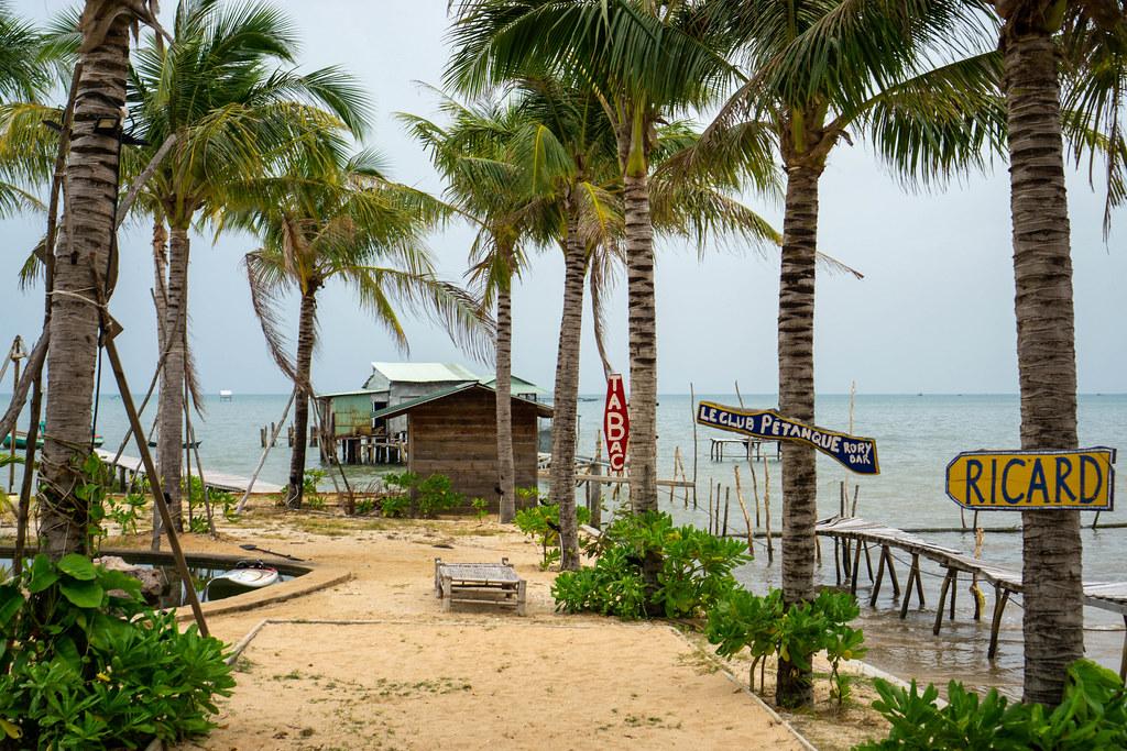 Sandstrand neben einem Naturschwimmbecken umgeben von Palmen bei Rory