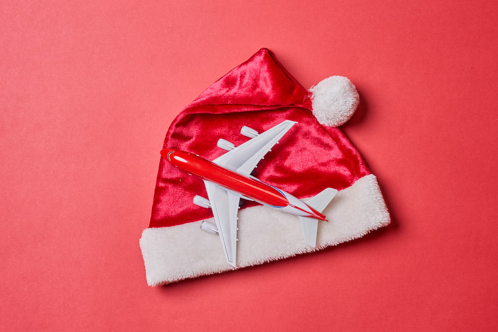 Santa Claus cap and toy airplane on red