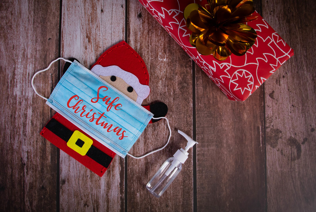 Santa Claus with medical face mask, sanitizer and gift box on wooden background