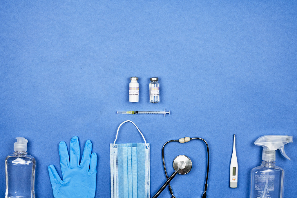 Sars-CoV-2 vaccine doses, face mask and medical equipment on blue background with copy space
