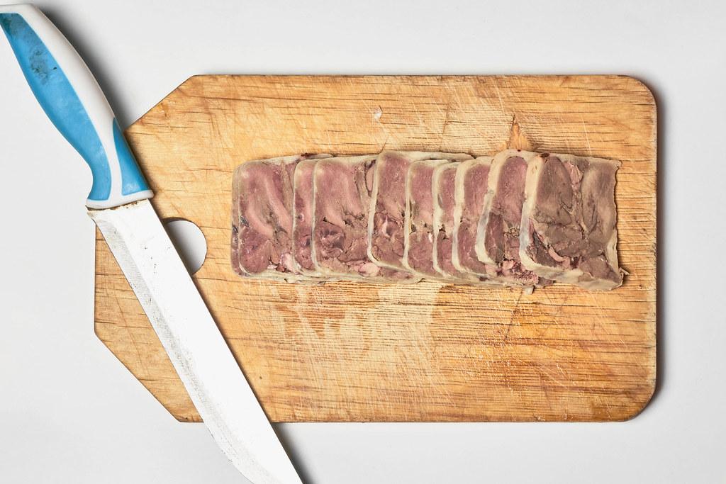 Scheiben von geräucherter Rinderzunge mit einem Messer auf einem Holzbrett. Aufnahme von oben