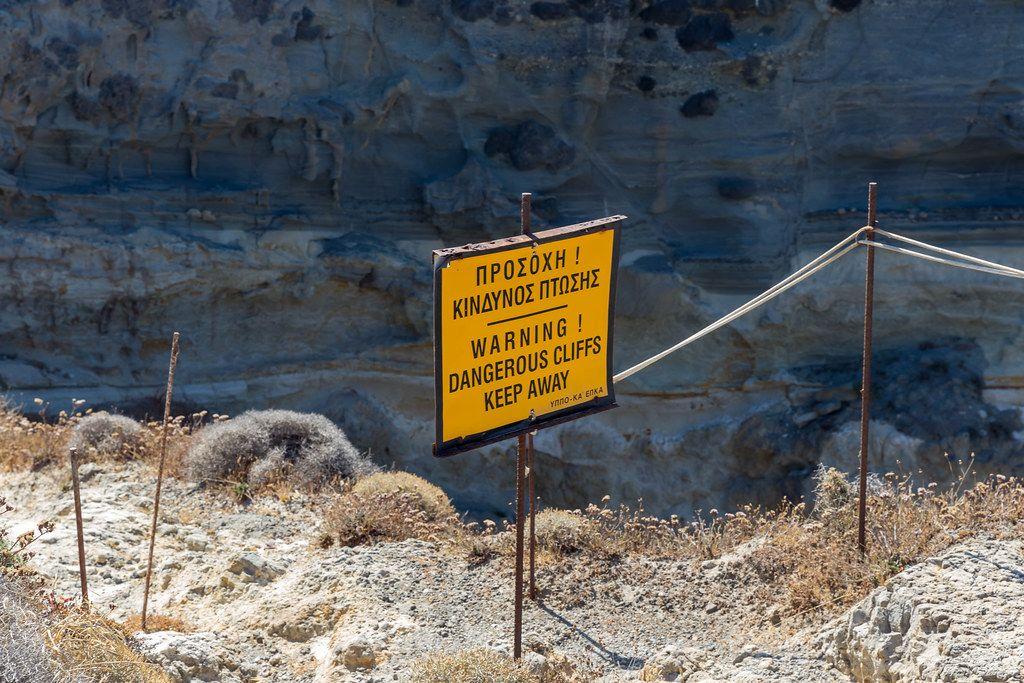 Schild auf Griechisch und Englisch warnt Touristen vor Gefahr auf der Klippe in Papafrangas auf Milos