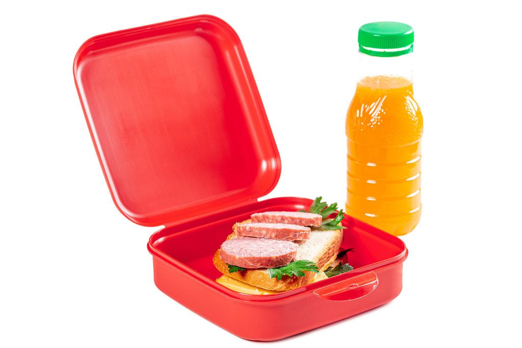 School lunch box - with a fresh sandwich and a bottle of orange juice