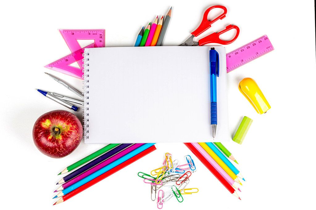 School supplies and red apple on white, colored school background