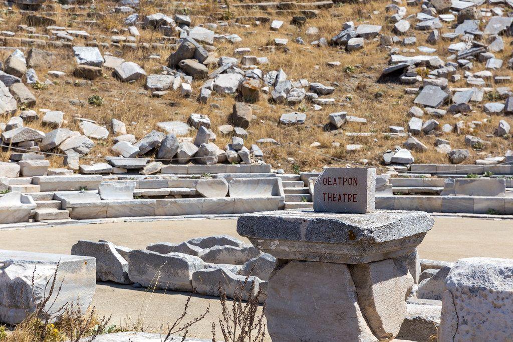 Schrift auf Griechisch und Englisch auf einem Stein beim antiken Theater von Delos